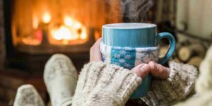 A close up shot of somebody holding a hot cup of tea and keeping warm at home in front of the fire.