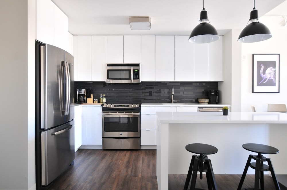 A White Glossy Kitchen With Black Lights