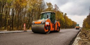 A bright orange roller smoothing a new road with bitumen.