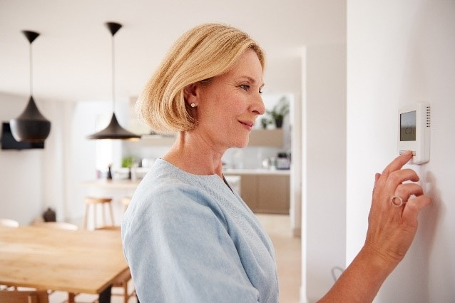 A woman turning down her thermostat at home for a lower heating bill.
