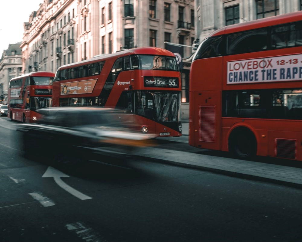 Red London buses going down a busy road.