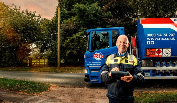 A Rix OFTEC engineer smiling at the camera, standing in front of his truck with a clipboard.