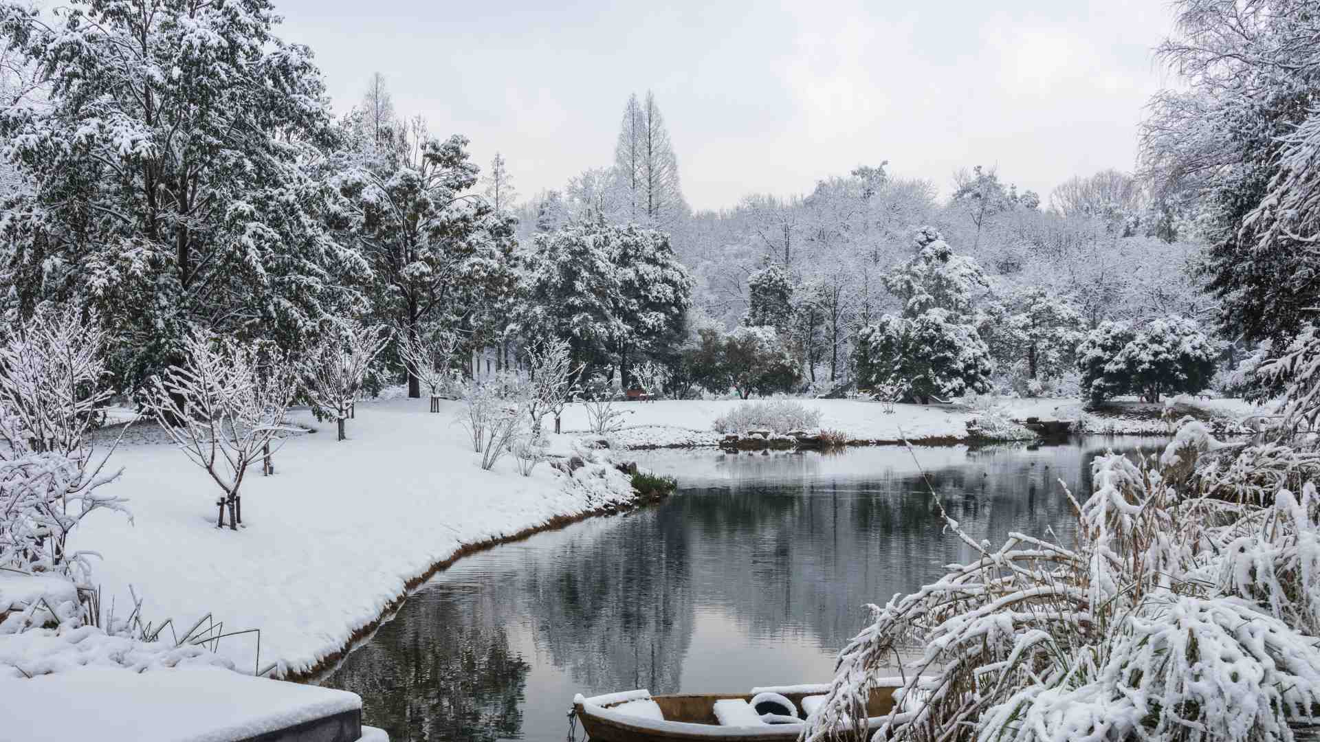 A snowy, winter landscape with snow-covered trees, a lake and a small boat.