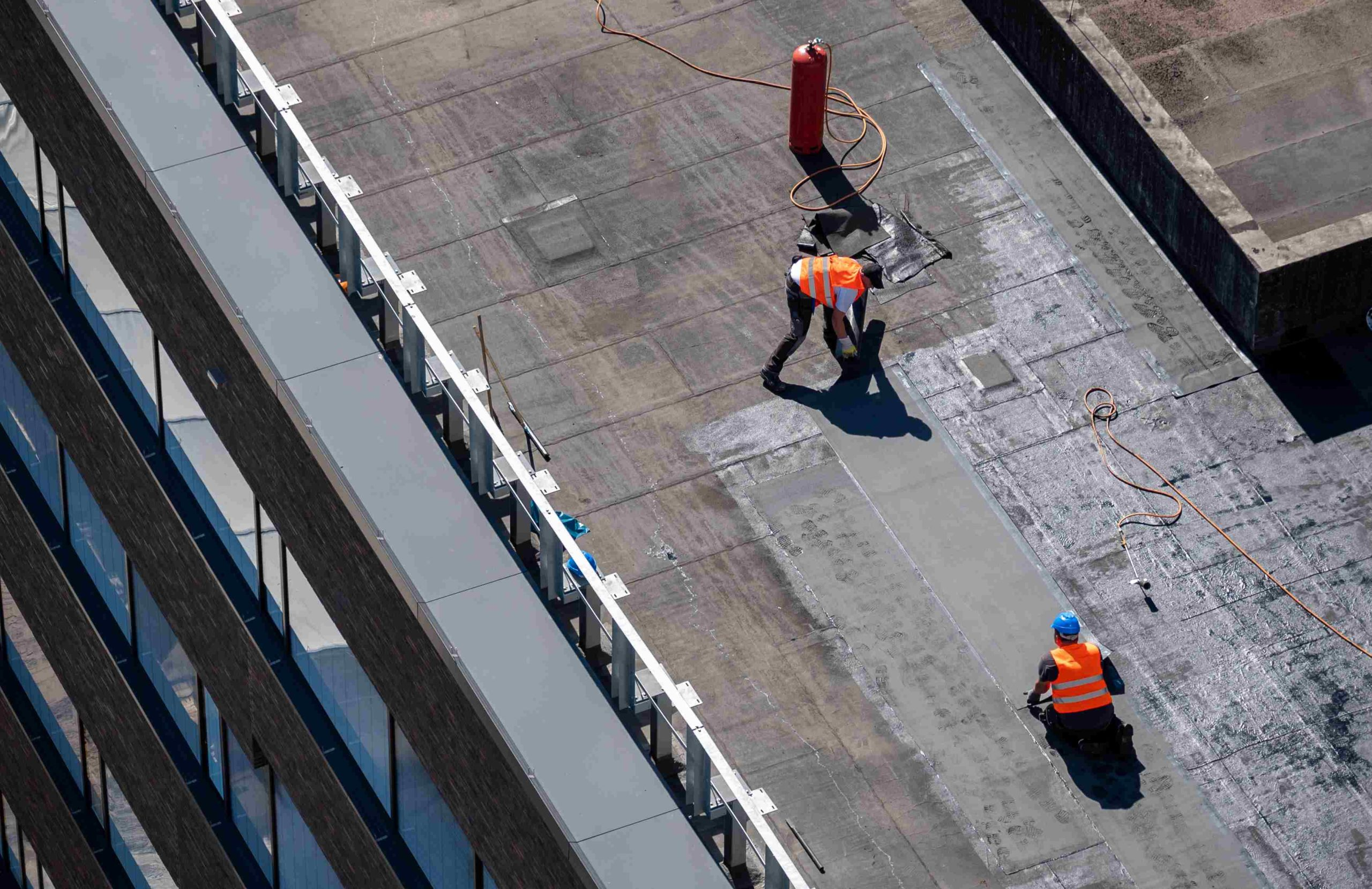 Workers laying bitumen on a building's roof. Bitumen can be used for roofing in order to protect the building from water penetration and damp.