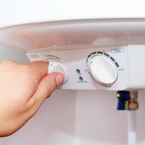A Hand Turning The Dials On A Boiler