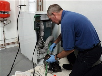A Male Engineer In A Blue Top Servicing A Boiler