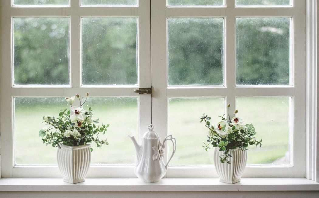 Windows with white framing looking onto a garden. There is a windowsill with two white flower vases and a white teapot ornament. The type of windows you have is an important factor when it comes to choosing the right boiler.