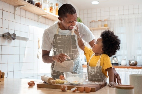 A father and his child baking together and smiling at each other.